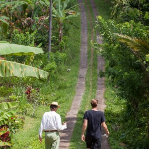 will and his friend Giuseppe walking in a cocoa plantation